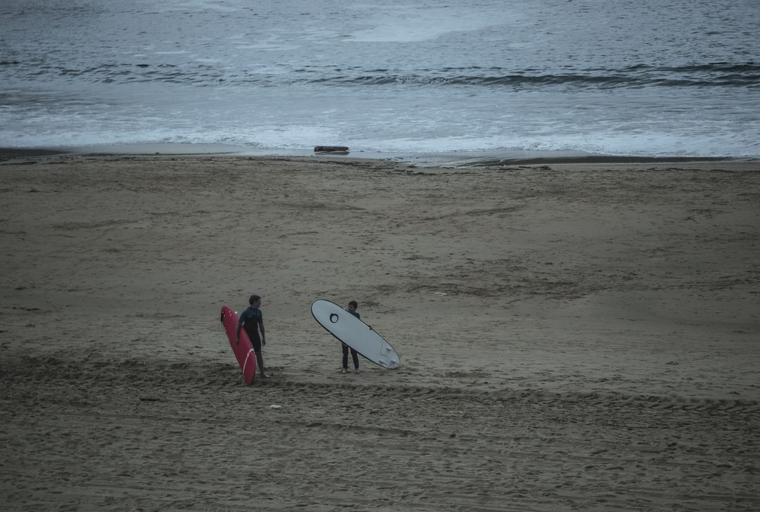 A man in a wet suit carrying a surf board on a beach