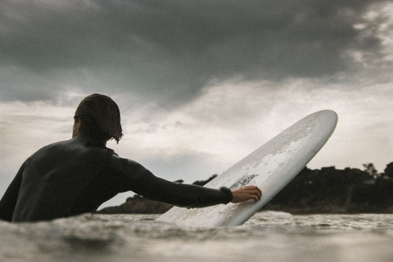 A man is surfing on a large body of water