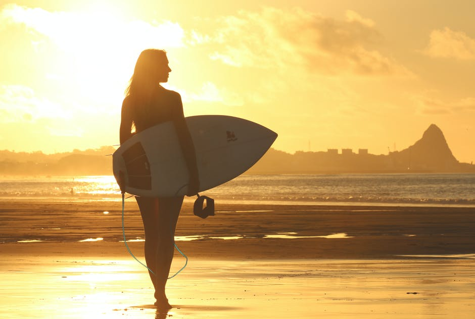 A person carrying a surf board walking on a beach